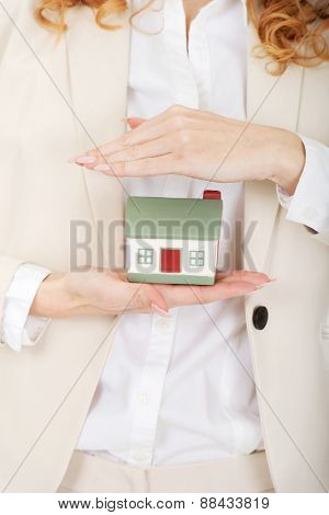 Young businesswoman presenting a model house.