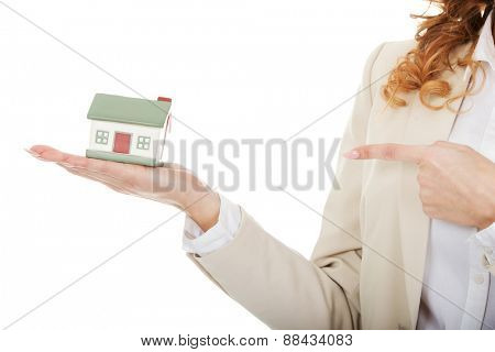 Businesswoman pointing on a model house in hand.