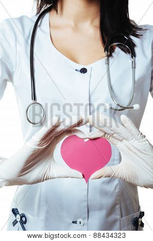 Positive female doctor standing with stethoscope and red heart symbol isolated on white background