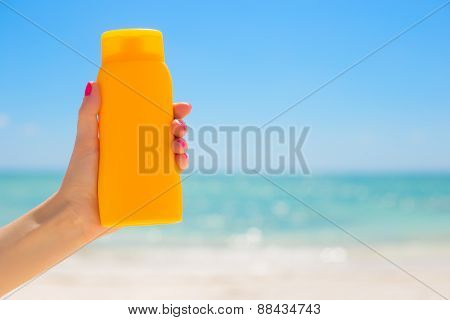 Woman holding sunscreen bottle