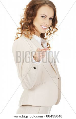 Happy businesswoman pointing on camera.