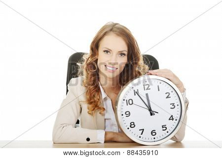 Happy businesswoman with clock by a desk.