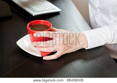 Woman hands on red cup of coffee on an office table