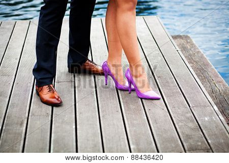 Elegant couple's legs on wooden pier