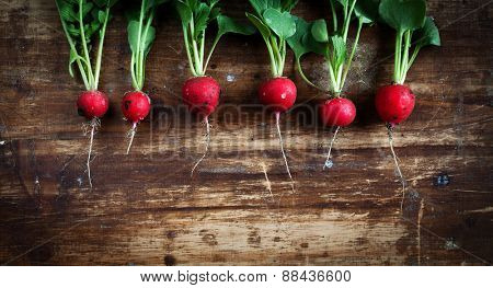 Bunch of fresh radishes on old wooden table