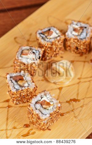 Japanese cuisine - sesame sushi rolls with syrup