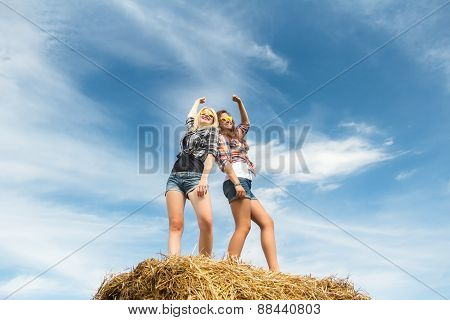 Two girls dancing in full length on straw bale