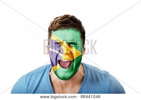 Screaming man with Brasil flag painted on face.