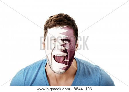 Screaming man with Qatar flag painted on face.