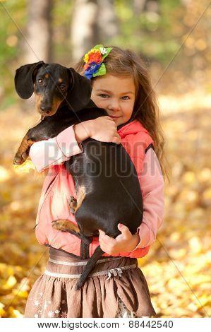 Little Kid Hugging Dachshund Puppy.