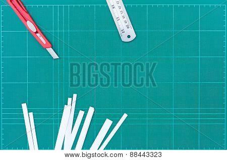 A Ruler And Cutter On Green Cutting Mat