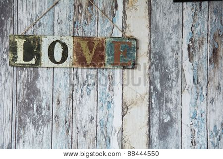 A Sign With The Word Love On The Background Of Old Wall From Boards.