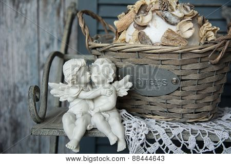 Figurines Angels Sitting On A Bench Near The Wicker Basket
