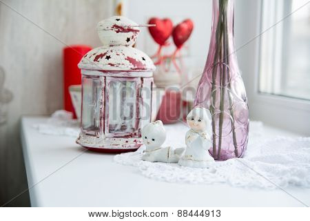 Close-up Of Porcelain Figurines With Flowers On The Windowsill And Old Lantern For Candles