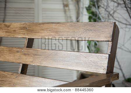 Close-up Of Brown Lacquered Bench On The Background Of Bright Wall With Tree Branches