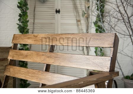 Brown Lacquered Bench On The Background Of Bright Wall With Tree Branches