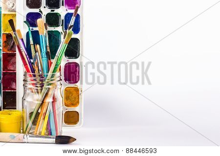 isolated paints brushes in glass and paint palette