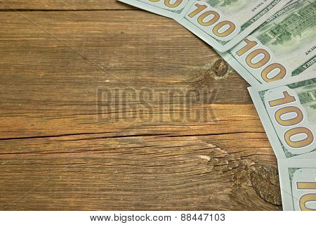 Five One Hudred Dollar Bill On The Rough Wood Background