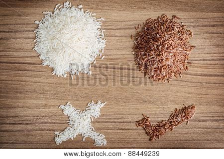Brown Rice And Rice On Wooden Background