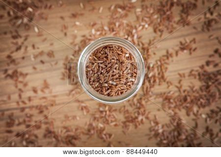 Brown Rice In Glass On Wooden Background
