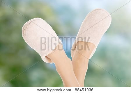 Female's feet wearing comfortable white slippers.