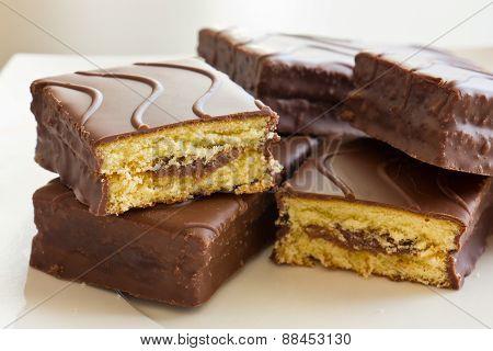 Sliced sponge cake in chocolate