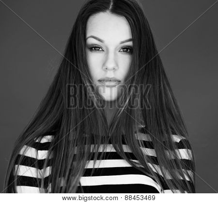 Close up Gorgeous Young Woman with Long Straight Hair, Wearing Striped Shirt, Looking at the Camera in Monochrome Color.