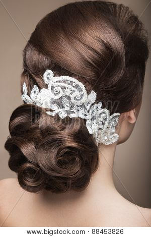 Portrait of a beautiful woman in the image of the bride with lace in her hair. Hairstyle back view