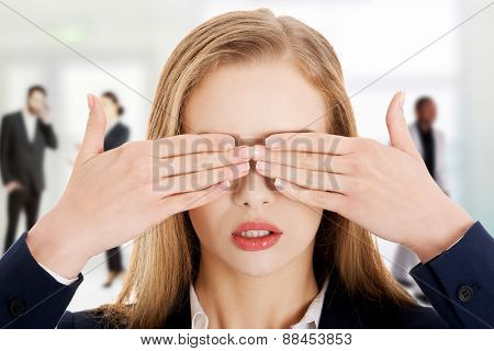 Caucasian businesswoman covering eyes with hands.