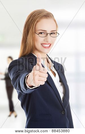 Businesswoman showing thumbs up with hand.
