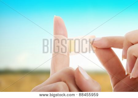 Woman apply aid plaster on finger.
