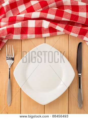kitchen utensils and cloth napkin on wooden background