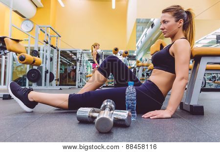 Woman resting and friend doing dumbbells exercises on gym
