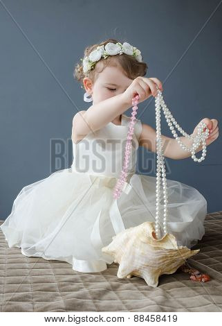 Beautiful little girl in white dress playing with beads