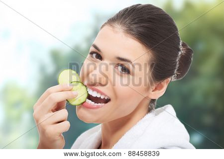 Beautiful woman in bathrobe eating slices of cucumber.