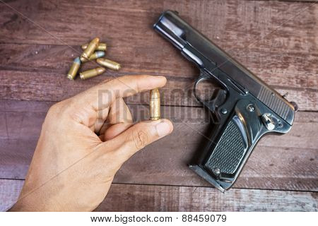 Hand With Bullet And Semi-automatic 9Mm Gun On Wooden Background