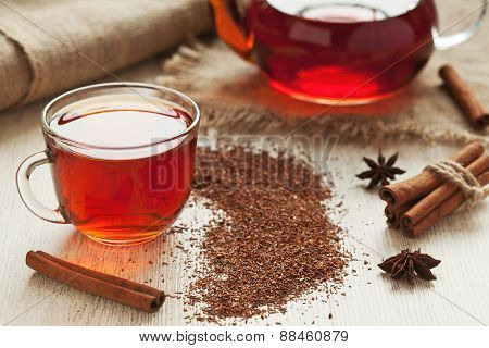 Healthy african rooibos tea in glass cup with spices on vintage table