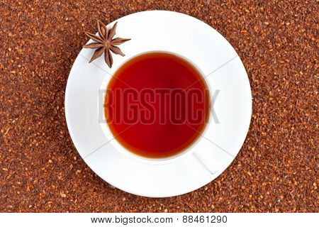 Red traditional rooibos tea full of antioxidant in white cup with star anise