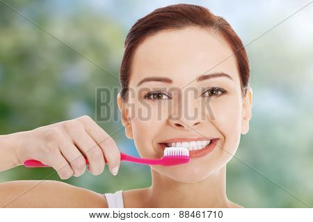 Beautiful happy woman brushing teeth.