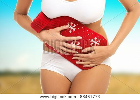 Woman with hot water bottle suffering from stomach pain.