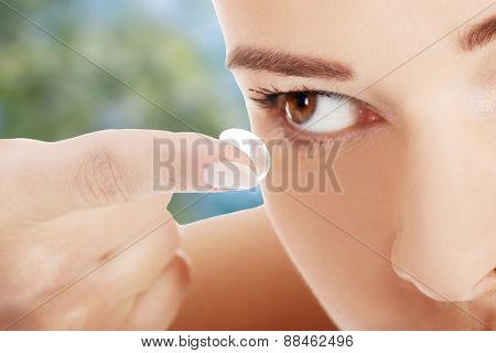 Young woman putting contact lens.