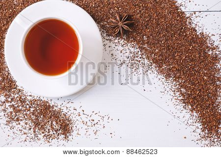 Top view of red traditional African rooibos tea in white cup with star anise