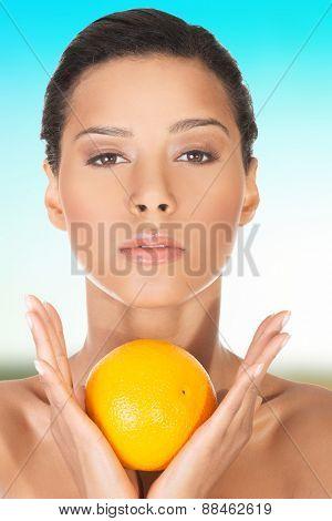 Beautiful slim woman with an orange.