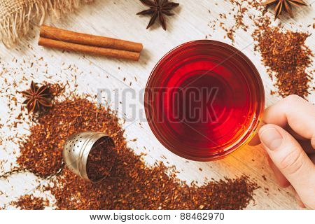 Unrecognizable man holding cup of african rooibos tea