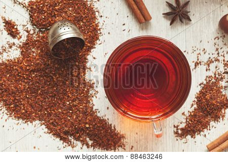 Cup of tasty organic herbal rooibos red tea with spices on vintage table