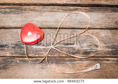A Measuring Tape Shaping A Heart On Wooden Background