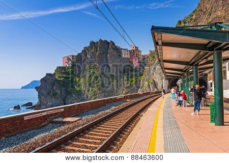 MANAROLA, ITALY - APRIL 11, 2015: People waiting for a Cinque Terre train in Manarola, Italy. The Cinque Terre National Park is in the Liguria region of Italy with five famous coastline villages.