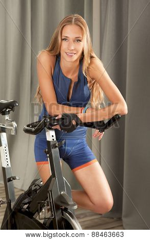 Beautiful young woman in sports outfit standing next to a spin bicycle in a jim.