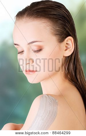 Beautiful woman with clay on shoulder.