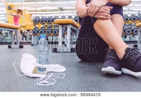 Sporty woman sitting with dumbbells, water and smartphone in gym floor